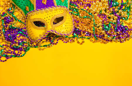 A venetian, mardi gras mask or disguise on a yellow background Standard-Bild