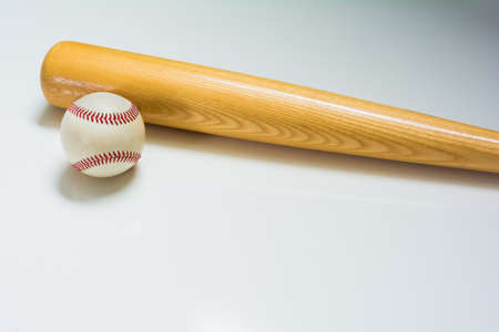 scuff: A leather baseball and wooden bat on a white background