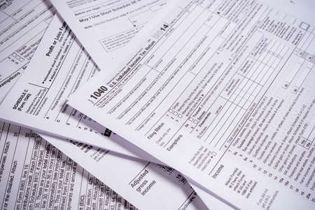A variety of United States tax forms with a pencil Foto de archivo