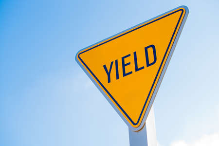 A yellow yield sign with a blue sky background
