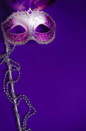 A purple mardi gras mask on a purple background with beads.  Carnivale costume. Standard-Bild