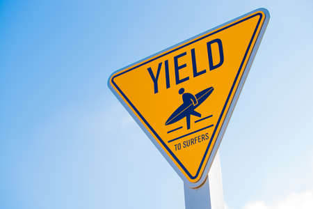 yield: A yellow yield to surfer sign in southern California Stock Photo