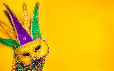 A venetian, mardi gras mask or disguise on a yellow background Stock Photo