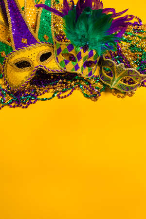 disguise: A group venetian, mardi gras mask or disguise on a yellow background with strings of beads