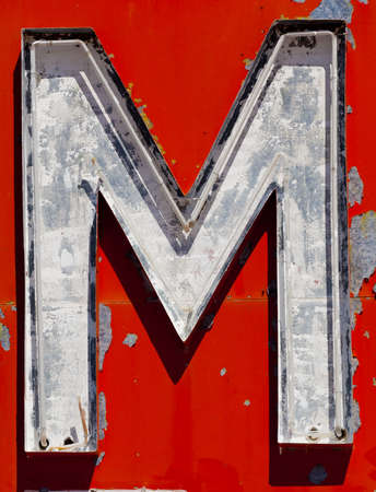 rundown: Vintage, run-down, antique letter M on a red, flaky painted background Stock Photo