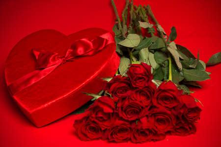 rosas rojas: Una caja del caramelo de San Valentín y rosas rojas sobre fondo rojo