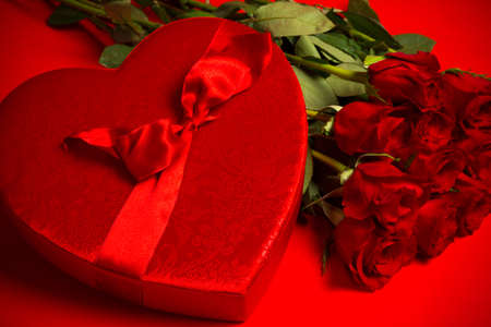 long stem roses: Long stem red roses and box of candy on a red background.  Valentines day gift, symbol of love and passion Stock Photo