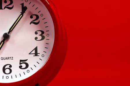 Rode klok alaram op een rode achtergrond met exemplaarruimte Stockfoto