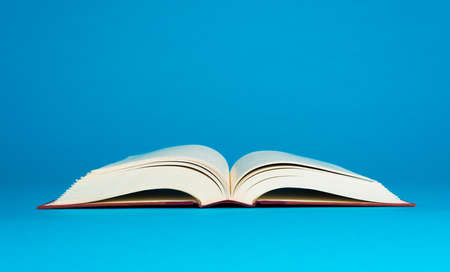 Open book on a blue background with copy space