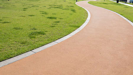paved: A walking path in a park making an S curve with grass