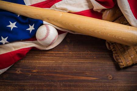 木製ベンチのヴィンテージ野球道具と古い、アンティークのアメリカの国旗