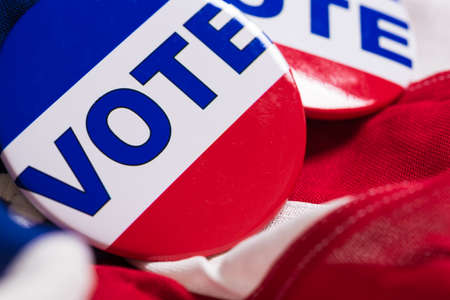 A VOTE pin or button on a flag of the United States Reklamní fotografie
