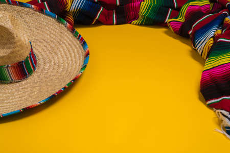 serape: A traditional Mexican Sombrero and serape blanket on a yellow background with copy space