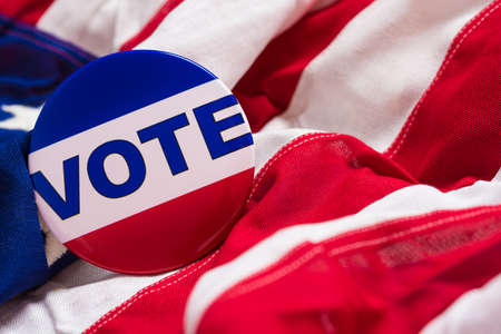 admonition: A VOTE pin or button on a flag of the United States Stock Photo