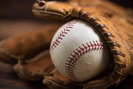 木製ベンチの茶色の革野球グローブ 写真素材