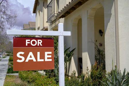Ein Schild zum Verkauf von Immobilien in der Reihe des Hauses Standard-Bild