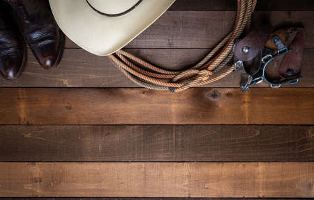 A group of American Cowboy Items incluing a lasso spurs and a traditional straw hat on a wood plank background