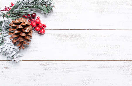 Christmas decorations on a white wood background with copy space. Pine cones, garland, berries and pine branches 版權商用圖片