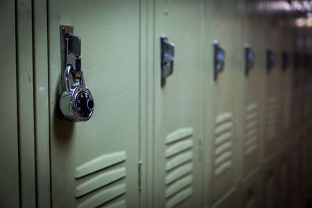 A row of green school lockers with a padlock Stock Photo