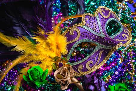 Colorful Mardi Gras mask on purple background with beads Standard-Bild