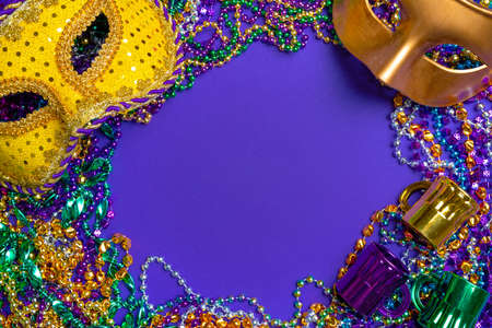 Colorful Mardi Gras or carnival mask on a purple background with beads.