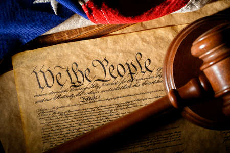 The American constitution, a wooden gavel and an American flag