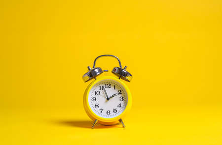 A yellow classic alarm clock on a yellow seamless p paper background