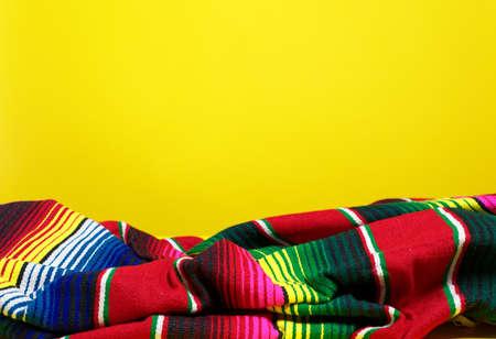 Una colorida manta de sarape mexicano sobre un fondo amarillo Foto de archivo