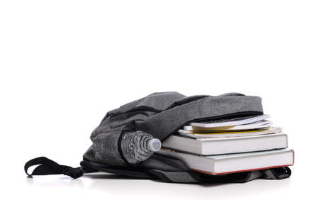 A gray School backpack on a white background with books and spiral notebooks