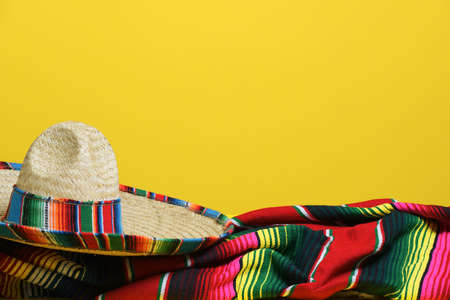 A straw Mexican sombrero on a colorful serape blanket on a yellow background. Cinco de Mayo