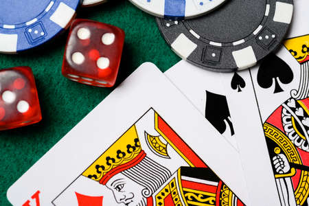 A group of poker chips, dice, playing cards on a green felt backgroud. Gambling, risk theme. Stock Photo