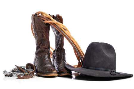 A pair of western cowboy boots and a lariat rope and spurs and a cowboy hat on a white background