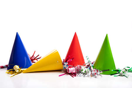 A group of colorful birthday hats and nose makers on a white background
