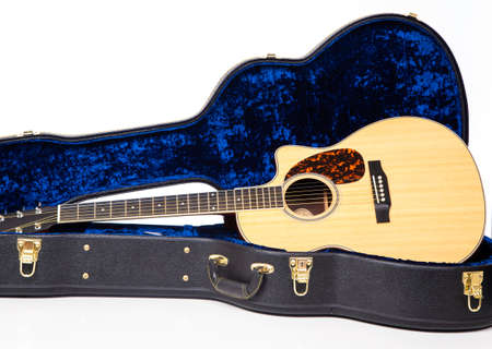 A classic wooden steel string guitar on a in case on a white background Banco de Imagens