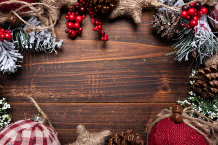 Christmas decorations on a brown wood background with copy space. Pine cones, garland, berries and pine branches 스톡 콘텐츠
