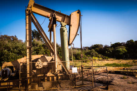 An oil industry pump jack pumping oil in an oil patch in California