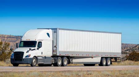 Eighteen wheel big rig tractor with trailer on highway. Trucking industry