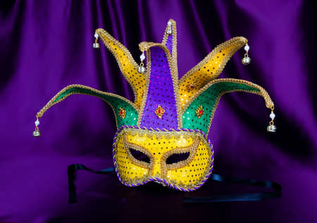 Colorful Mardi Gras mask on purple background with beads
