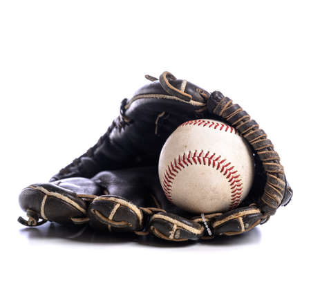 A leather baseball glove and ball on a white background