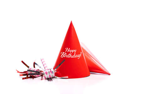 Red paper birthday hats and noise-makers on a white background.