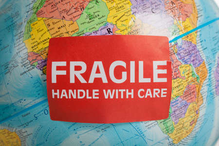 An Earth globe with a fragile hand with care sticker 스톡 콘텐츠