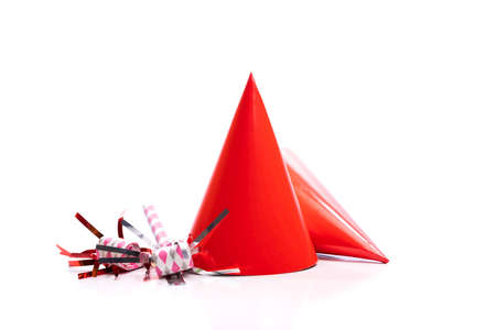 Red birthday hats and noise-makers on a white background.