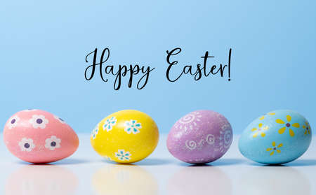 Colorful Easter eggs on blue background with greeting