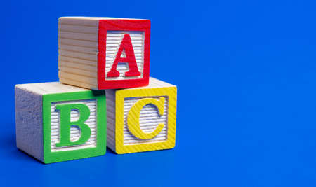 Wooden ABC blocks on blue background