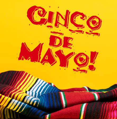 Mexican Serape blanket on yellow background with Cinco de Mayo.