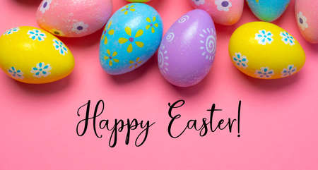 Colorful Easter eggs on pink background with greeting 스톡 콘텐츠