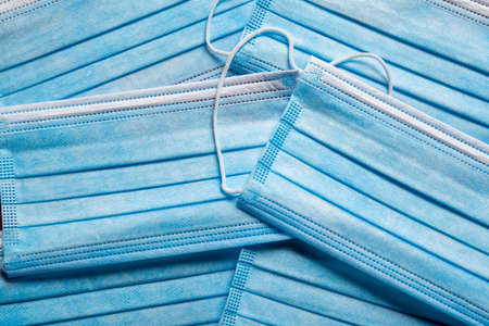 A stack of blue paper surgical masks. COVID, virus theme