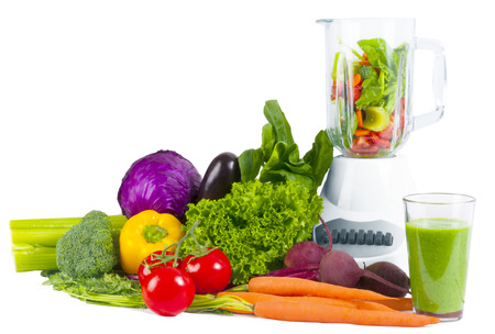 Blender with fresh vegetable, and glass of juice on a  background Stock Photo