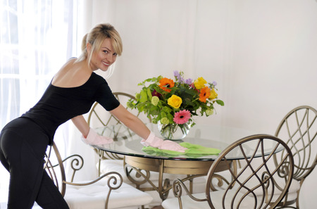 Cleaning in house woman clean table, on table flowers. Smiling cleaning lady in pink rubber gloves during work Stock Photo