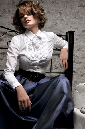 long skirt: Beautiful woman in long skirt and white blouse, sitting on sofa in studio Stock Photo
